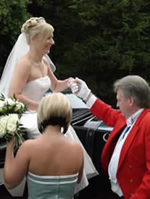 English toastmaster assisting a bride from a horse drawn carraige at the wedding reception at The Park Hotel, Lakeside, Essex